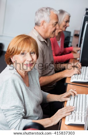 Happy Senior Woman Using Computer In Classroom