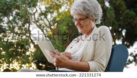 Happy senior woman using tablet at the park - stock photo