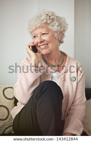 Happy senior woman with a cell phone sitting at home - stock photo