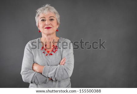 Happy senior woman with arms crossed over grey background isolated. - stock photo