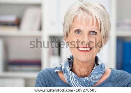 Happy senior woman with beautiful blue eyes wearing a stylish scarf standing in an office smiling at the camera