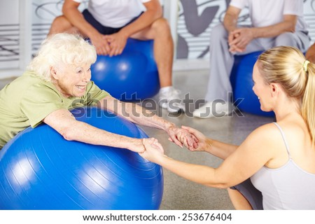 Happy senior woman with fitness instructor in rehab center - stock photo
