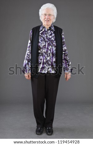 Happy senior woman with glasses against grey wall. Studio shot. - stock photo