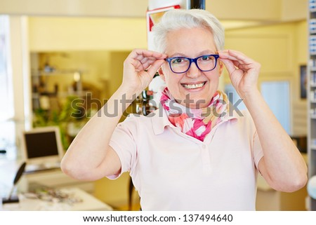 Happy senior woman with her new glasses at the optician - stock photo