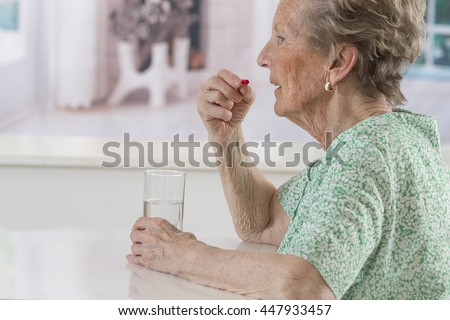 happy senior woman with pills glass of water at home