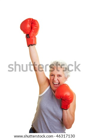 Happy senior woman with red boxing gloves - stock photo