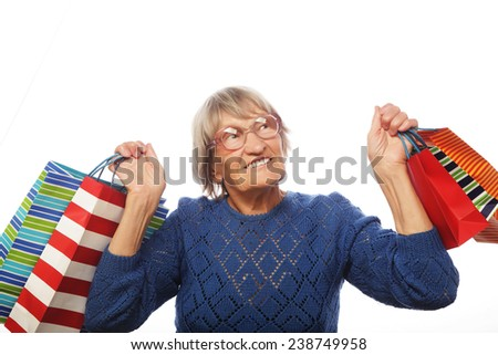 Happy senior woman with shopping bags isolated on white - stock photo