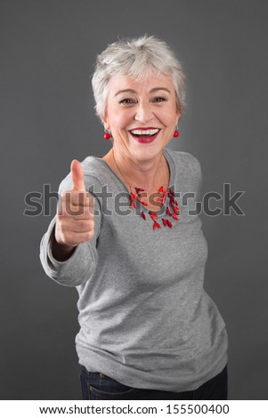 Happy senior woman with thumbs up