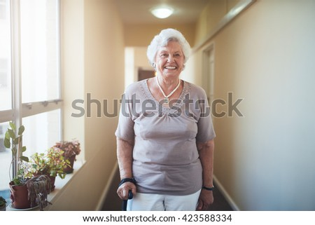 Happy senior woman witPortrait of happy senior woman with walking stick standing at home. Caucasian female looking at camera and smiling.h walking stick standing at home - stock photo