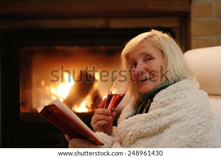 Happy senior woman, wrapped in warm knitted plaid, relaxing at home in the evening, sitting in rocking chair, drinking wine, reading book and enjoying fireplace - successful retirement concept - stock photo