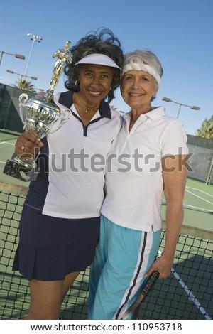 Happy senior women holding trophy on tennis court - stock photo