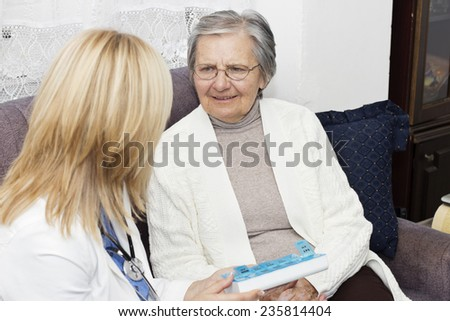 Happy senior women sitting on the sofa and talking with her home caregiver. - stock photo