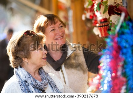 Happy senior women walking on the Christmas market and choosing jewelry. Focus on the left woman - stock photo