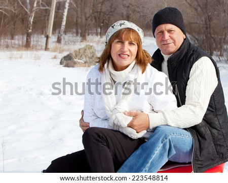 Happy seniors couple in winter park. Elderly mature people - stock photo