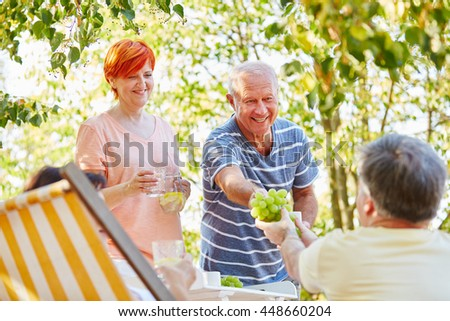 Happy seniors making a picnic with fruits in the garden