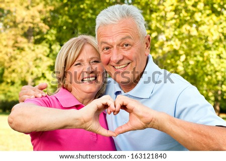 Happy seniors posing with holding hands and smiling.  - stock photo