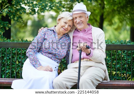 Happy seniors sitting on bench and having rest in the park - stock photo