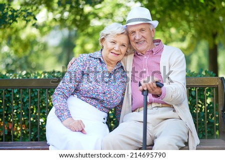Happy seniors sitting on bench in the park and enjoying rest - stock photo