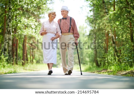 Happy seniors taking a walk in the park on sunny day - stock photo