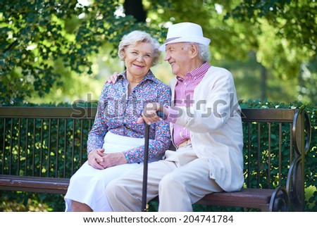 Happy seniors talking while sitting in the park - stock photo