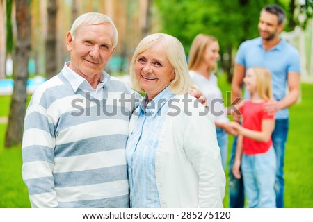 Happy seniors with family. Happy senior couple bonding and looking at camera while other family members standing in the background  - stock photo