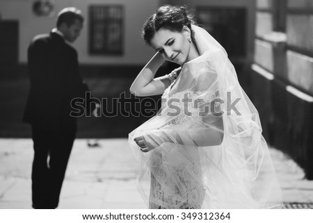 Happy sensual brunette bride with veil posing outdoors with groom in background b&w - stock photo