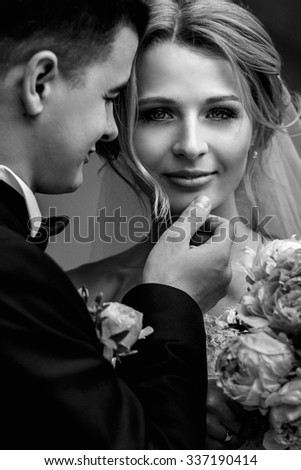 Happy sensual handsome groom and blonde beautiful bride in white dress hugging  b&w