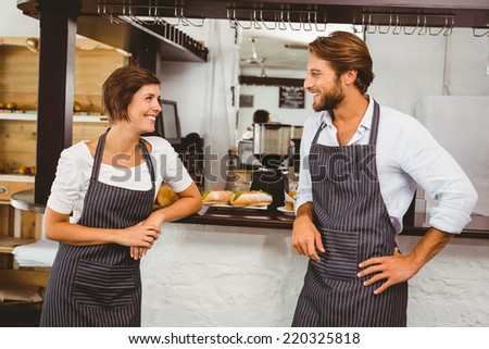 Happy servers chatting at the counter at the coffee shop - stock photo
