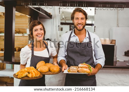 Happy servers holding plates of food at the coffee shop - stock photo
