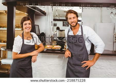 Happy servers smiling at camera at the coffee shop - stock photo