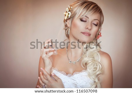 Happy sexy beautiful bride blond girl in white wedding dress with hairstyle and bright makeup and perfume bottle. Romantic lady in bridal dress and flowers in hair have final preparation for wedding - stock photo