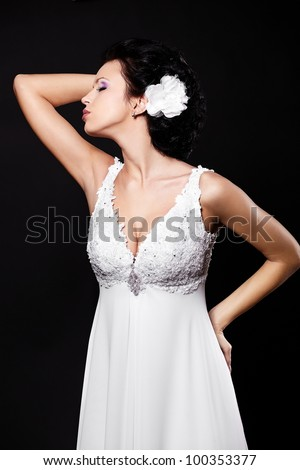 Happy sexy beautiful bride brunette girl in white wedding dress with hairstyle and bright makeup with flower in hair isolated on black