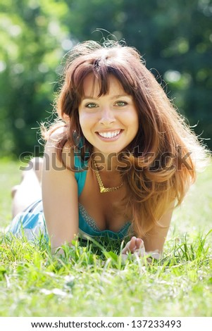 Happy sexy girl lying outdoor in grass meadow