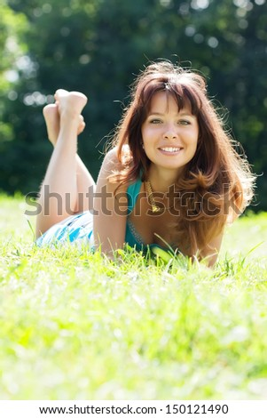 Happy sexy girl lying outdoor in grass meadow  - stock photo