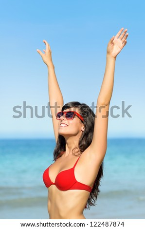 Happy sexy woman bliss on summer holidays. Beautiful brunette girl towards the sea raising arms to sky . - stock photo