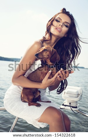 happy sexy woman with dog on the luxury boat in open sea in summer. Caucasian female model. Outdoors, lifestyle. - stock photo