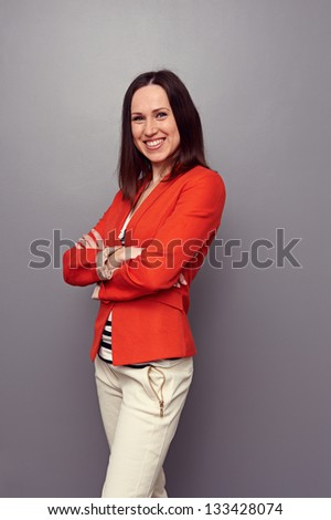 happy sexy woman with folded hands posing over dark background. studio shot