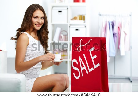 Happy shopaholic drinking coffee at shop with shopping bag from sale nearby - stock photo