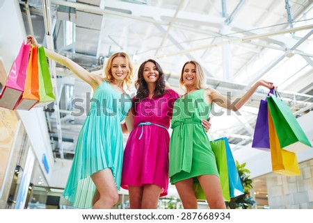 Happy shopaholics with paperbags looking at camera - stock photo