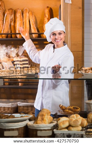 Happy shopgirl working in bakery with bread and pastry
