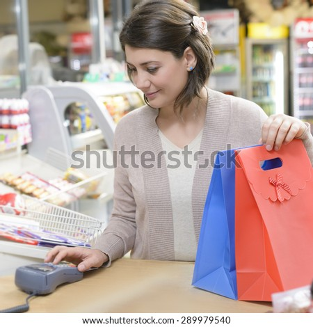 Happy Shopper at cash desk in a  market - stock photo