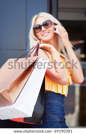 Happy shopper calling on the phone. - stock photo