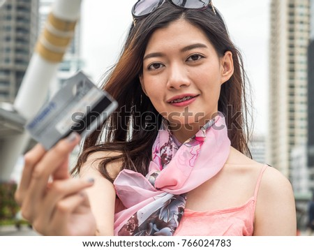 Happy shopper woman posing with shopping bags and holding credit card in hand on city background. Shopping concept