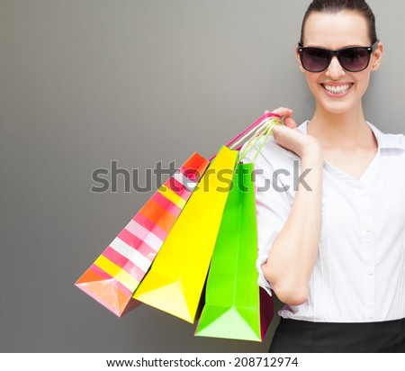 Happy shopping! Beautiful woman holding shopping back. - stock photo
