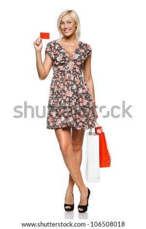 Happy shopping female holding blank credit card. Full length portrait.