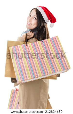 Happy shopping girl holding bags and wearing Christmas hat, half length closeup portrait on white background. - stock photo