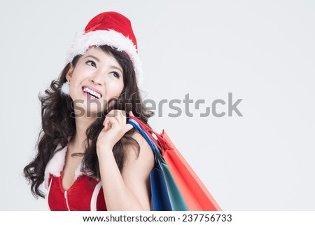 Happy shopping girl wearing Christmas clothes holding bags in department store,shopping, sale, gifts, christmas, x-mas concept - smiling woman in red dress and santa helper hat with shopping bag