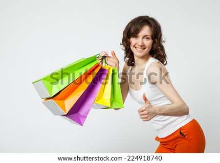 Happy shopping! Happy beautiful young woman holding multicolored shopping bags showing thumb up, white background - stock photo