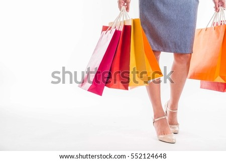 Happy shopping! Unrecognizable woman in gray skirt holding multicolored shopping bags