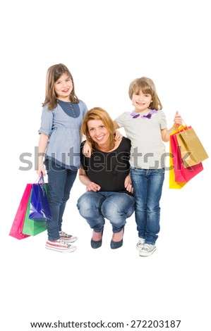 Happy shopping woman and her two daughters isolated on white background